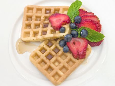Waffles with fresh berries on a white plate photo