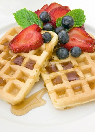 Waffles on a white plate with strawberies, blueberries, and syrup.