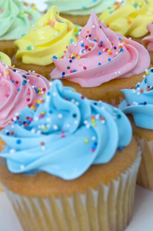 Colorful frosted cupcakes with candy sprinkles.  Focus on the pink cupcake. Imagens