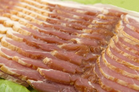 uncooked bacon: Raw sliced bacon uncooked side view on a bed of greens.