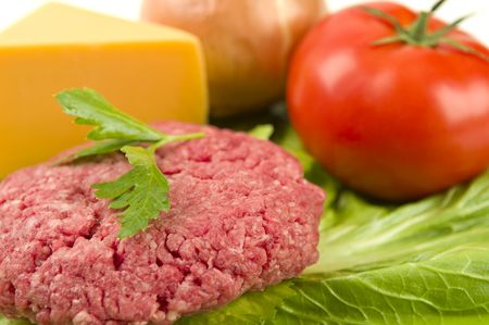 Raw hamburger patty with raw toppings.  Focus on front of hamburger patty.