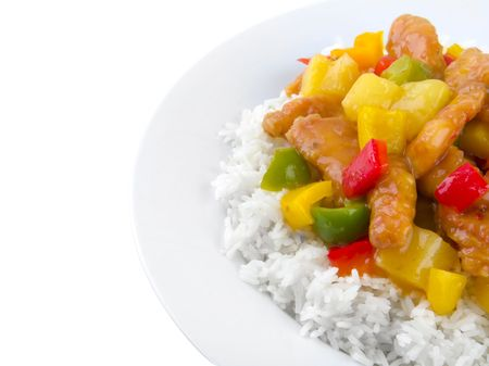 Sweet and sour chicken on a white plate with copy space on left side.