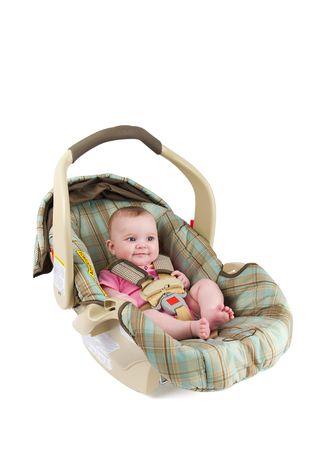 Een gelukkig baby meisje zit in een auto stoel geïsoleerd op een witte achtergrond