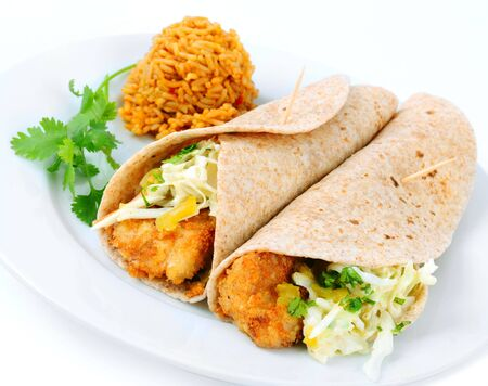 tilapia: A pair of fish tacos served with spanish rice on a white background