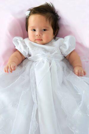 bautismo: Niña bebé recién nacido en un vestido de blanco de bautismo en una manta de color rosa