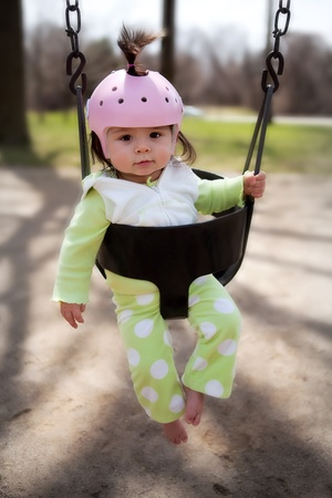 An infant in a playground swing with a protective helmet photo