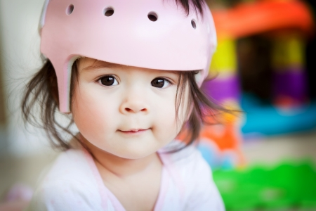 A baby girl with an orthopedic helmet smiles for the camera photo