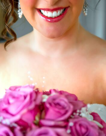 A smiling bride to be holds a flower bouquet before the wedding