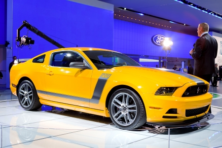 DETROIT - JANUARY 11: A reporter talking about the 2013 Ford Mustang Boss 302 at the 2012 North American International Auto Show Industry Preview on January 11, 2012 in Detroit, Michigan.