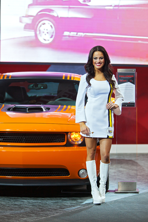 american media: DETROIT - JANUARY 13 : A mdeol poses with the Dodge Challenger at the North American International Auto Show media preview  January 13, 2014 in Detroit, Michigan.