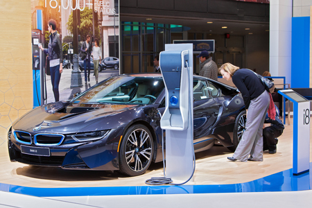 DETROIT - JANUARY 15: A visito looking at the BMW i8 electric vehicle  January 13th, 2015 at the 2015 North American International Auto Show in Detroit, Michigan.