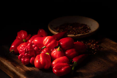 Assorted hot chilli pepper and crushed peppers on wooden surface. Ideal for food recipe or restaurant menu