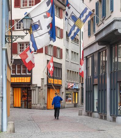 alphorn: Zurich, Switzerland - 1 August, 2014  a person carrying an alphorn passes an old town street  The Swiss National Day  German  Schweizer Bundesfeier  is the national holiday of Switzerland, set on 1 August  Editorial
