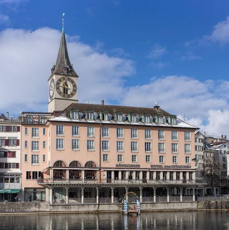 Zurich, Switzerland - 1 February 2015: St. Peter Church and hotel zum Storchen building. Zurich is the largest city in Switzerland and the capital of the canton of Zurich. Sajtókép