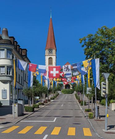 german swiss: Wallisellen, Switzerland - 2 August, 2015: the Kirchstrasse street decorated with flags for the Swiss National Day. The Swiss National Day German: Schweizer Bundesfeier is the national holiday of Switzerland, celebrated on 1 August. Wallisellen is a subur
