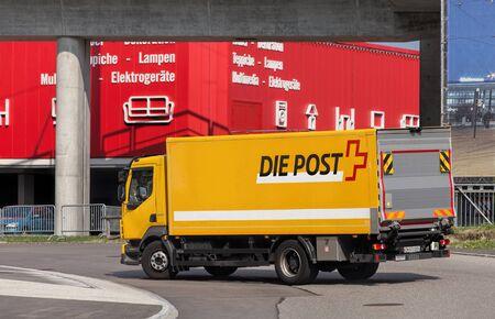 public company: Wallisellen, Switzerland - 11 August, 2015: a Swiss Post truck on the road. Swiss Post French: La Poste suisse, Italian: La Posta Svizzera, German: Die Schweizerische Post, Romansh: La Posta Svizra is a public company owned by the Swiss Confederation prov