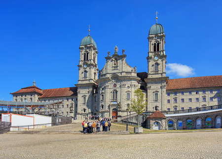 hermits: Einsiedeln, Switzerland - 8 September, 2015: tourists at entrance of the Einsiedeln Abbey. Einsiedeln Abbey is a Benedictine monastery in the town of Einsiedeln in the Canton of Schwyz, Switzerland. The abbey is dedicated to Our Lady of the Hermits, the t Editorial