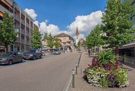 Wallisellen, Switzerland - 6 September, 2014: view along the Bahnhofstrasse and Kirchstrasse streets with the protestant church in the background. Wallisellen is a municipality in the district of Bulach in the canton of Zurich in Switzerland, belonging to
