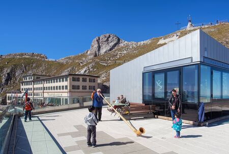 alphorn: Mt. Pilatus, Switzerland - 23 September, 2014: tourists watching a person playing the alphorn. Alphorn or alpenhorn or alpine horn is a wind instrument, consisting of a wooden natural horn of conical bore, having a wooden cup-shaped mouthpiece, used by mo