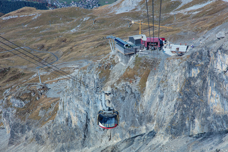 cantons: Mt. Titlis, Switzerland - 12 October, 2015: cable car gondola heading downwards from the top of the mountain. Titlis is a mountain of the Uri Alps, located on the border between the cantons of Obwalden and Bern. At 3,238 metres above sea level, it is the