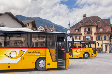 Ilanz, Switzerland - 24 July, 2009: Post buses at the stop at the Ilanz railway station. PostBus Switzerland PostAuto Schweiz in German, CarPostal Suisse in French, and AutoPostale Svizzera in Italian is a subsidiary company of the Swiss Post, which provi