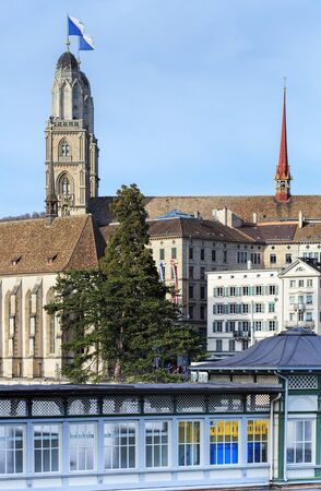 grossmunster cathedral: Zurich, Switzerland - 13 April, 2015: view with the Grossmunster cathedral in the background and the Frauenbad Stadthausquai building in the foreground. Frauenbad Stadthausquai is a public bath built in the end of the 19th century, it was built and is sti