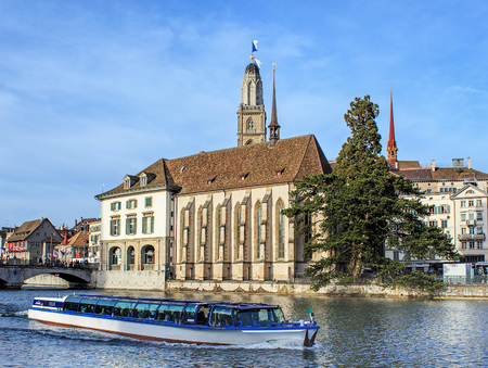 felix: Zurich, Switzerland - 13 April, 2015: Felix boat passing along the Limmat river with the Water Church and Grossmunster towers in the background. Zurich is the largest city in Switzerland and the capital of the Swiss canton of Zurich.