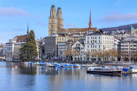 grossmunster cathedral: Zurich, Switzerland - 18 January, 2016: view over the Limmat river towards the Limmatquai quay with the Grossmunster cathedral in the background. Zurich is the largest city in Switzerland and the capital of the Swiss canton of Zurich. Editorial