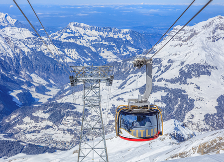 Mt. Titlis, Switzerland - 9 March, 2016: Rotair cable car gondola heading downwards, view from the station on the top of the mountain. Rotair gondolas make a 360 degrees turn during the five-minute trip. Titlis is a mountain of the Uri Alps, located on  Sajtókép