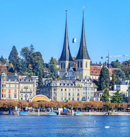 st german: Lucerne, Switzerland - 3 October, 2015: view on the Church of St. Leodegar (German: St. Leodegar im Hof or Hofkirche St. Leodegar) and the Nationalquai quay over Lake Lucerne. Lucerne is a city in central Switzerland, it is the capital of the Canton of Lu