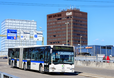 daimler: Wallisellen, Switzerland - 26 March, 2016: a bus passing the motorway bridge on the Neue Wintertuhrestrasse street with Allianz Suisse office and Glatt shopping center buildings in the background. Wallisellen is a municipality in the district of Bulach in