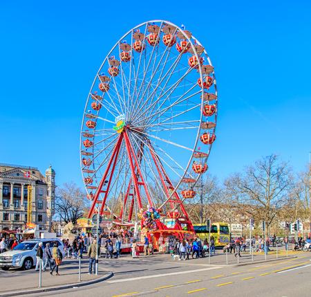 temporarily: Zurich, Switzerland - 10 April, 2016: Ferris wheel temporarily installed on Burkliplatz square in the center of the city. Zurich is the largest city in Switzerland and the capital of the Swiss canton of Zurich.
