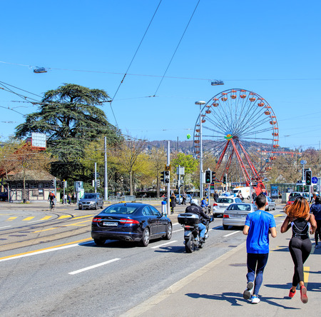 joggers: Zurich, Switzerland - 11 April, 2016: traffic and joggers on General Guisan quay with the Ferris wheel temporarily installed on Burkliplatz square in the background. Zurich is the largest city in Switzerland and the capital of the Swiss canton of Zurich.