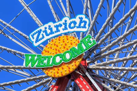 temporarily: Zurich, Switzerland - 10 April, 2016: central part of the Ferris wheel temporarily installed on Burkliplatz square with Welcome Zurich sign against blue sky. Zurich is the largest city in Switzerland and the capital of the Swiss canton of Zurich. Editorial