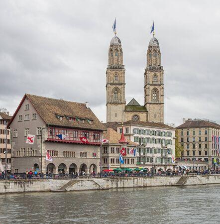 Zurych, Szwajcaria - 17 kwietnia 2016: ludzie na nabrzeżu Limmatquai i wieże Grossmunster urządzone flagami Zurychu podczas parady dzieci (niemiecki: Kinderumzug) poświęcony nadchodzącej uroczystości Sechselauten. Sechselauten jest tradycyjnym spr