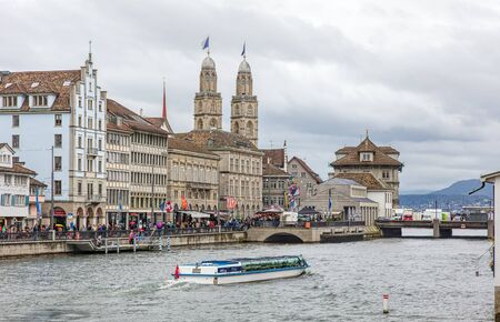 felix: Zurich, Switzerland - 17 April, 2016: people on the Limmatquai quay, Felix boat passing along the Limmat river and Grossmunster towers decorated with flags of Zurich during childrens parade (German: Kinderumzug) devoted to the upcoming Sechselauten fes