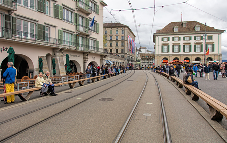 cel: Zurich, Switzerland - 17 April, 2016: people on the Limmatquai quay before beginning of childrens parade (German: Kinderumzug) devoted to the upcoming Sechselauten festivity. Sechselauten is a traditional spring holiday in the city of Zurich, usually cel