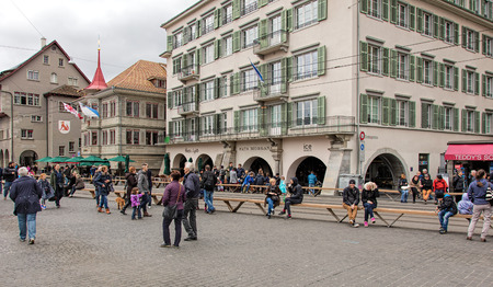 cel: Zurich, Switzerland - 17 April, 2016: people on the Limmatquai quay before beginning of childrens parade devoted to the upcoming Sechselauten festivity (German: Kinderumzug). Sechselauten is a traditional spring holiday in the city of Zurich, usually cel