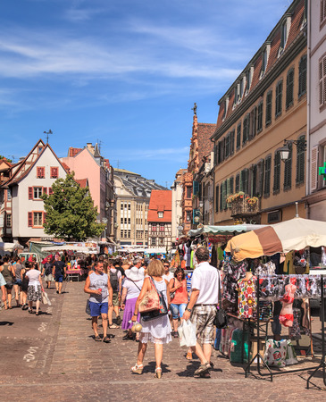 renowned: Colmar, France - 18 July, 2014: people on the street market in the old town. Colmar is the third-largest commune of the Alsace region in north-eastern France, renowned for its well preserved old town, numerous architectural landmarks and museums. Editorial