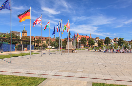 commune: Colmar, France - 18 July, 2014: flags and fountain on Place Rapp square. Colmar is the third-largest commune of the Alsace region in north-eastern France, renowned for its well preserved old town, numerous architectural landmarks and museums.