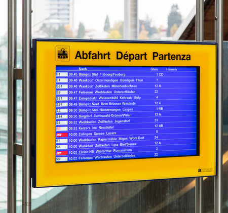 departure board: Bern, Switzerland - 19 October, 2015: departure board mounted on a transparent wall at one of the entrances of the Bern train station. The city of Bern is the capital of Switzerland and also the capital of the Swiss canton of Bern. Editorial