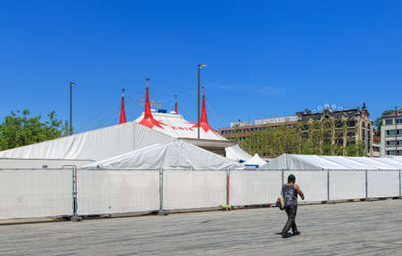 tent city: Zurich, Switzerland - 26 May, 2016: a person passing along the fence of Circus Knie temporarily installed on Sechselautenplatz square. Circus Knie is the largest circus of Switzerland, based in Rapperswil, founded in 1803 by the Knie family. Editorial