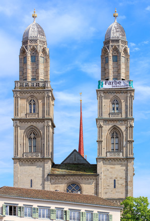grossmunster cathedral: Zurich, Switzerland - 25 May, 2016: towers of the Grossmunster cathedral with a banner, which is a part of the promotion devoted to the World Refugee Day on the 20th of June, arranged by aid organization of Evangelic Churches of Switzerland (German: Hilfs