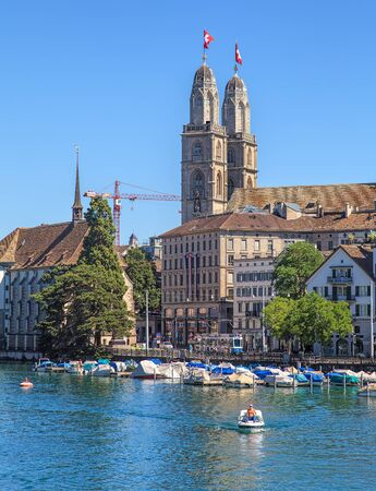1 person: Zurich, Switzerland - 1 August, 2013: a person in a boat on the Limmat river, towers of the Grossmunster cathedral decorated with flags of Switzerland in the background. Zurich is the largest city in Switzerland and the capital of the Swiss canton of Zuri