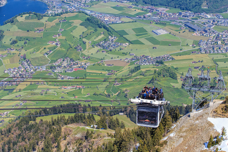 top 7: Mt. Stanserhorn, Switzerland - 7 May, 2016: people in a gondola of the Stanserhorn Cabrio cable car approaching the station on the top of the mountain.