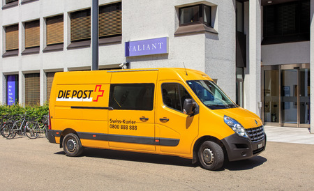 bank owned: Aarau, Switzerland - 7 July, 2016: a Swiss Post van parked at the entrance to the Valiant Bank office on Schlossplatz square. Swiss Post a public company owned by the Swiss Confederation, which provides national postal service for Switzerland, it is the c Editorial