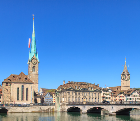 Towers of the Fraumunster Cathedral and St. Peter Church decorated with flags of Zurich and Switzerland and the Muensterbruecke bridge over the Limmat river in the city of Zurich, Switzerland.