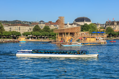 felix: Zurich, Switzerland - 20 July, 2016: Pavilion of Reflections on Lake Zurich, the Felix boat in the foreground, Zurich Opera House building in the background. The Pavilion of Reflections is a floating island with an open-air cinema and swimming pool. Editorial