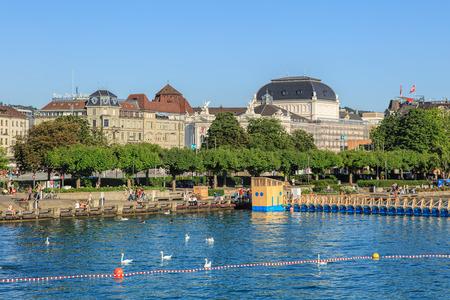 extending: Zurich, Switzerland - 20 July, 2016: view on Lake Zurich and the Utoquai quay, Zurich Opera House building in the background. Lake Zurich is a lake in Switzerland, extending southeast of the city of Zurich.