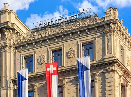 Zurich, Switzerland - 30 July, 2016: upper part of the Credit Suisse building on Paradeplatz square, decorated with flags of Switzerland and Zurich. Credit Suisse Group is a Swiss multinational financial services holding company, headquartered in Zurich. Sajtókép